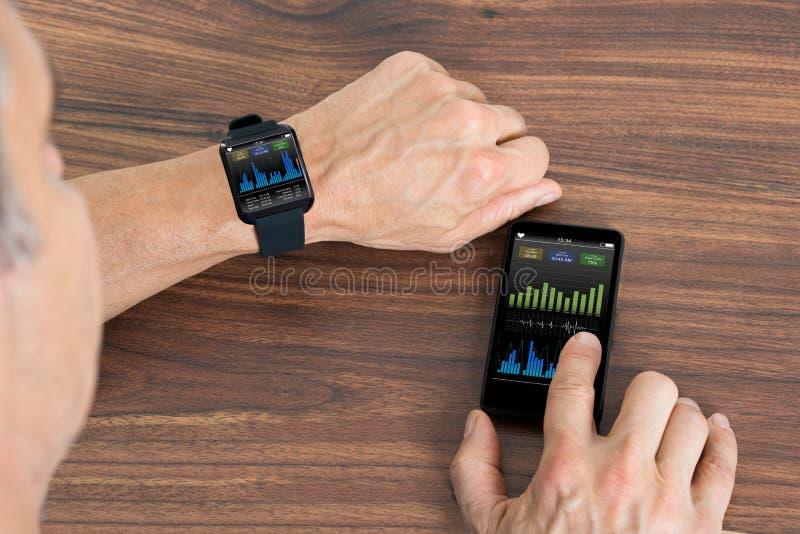 O homem com smartwatch e o telefone celular que mostra a pulsação do coração avaliam foto de stock