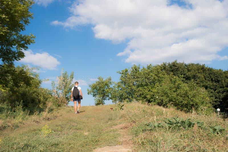 O homem com trouxa anda no monte no dia ensolarado Caminhando o conceito Viajante com a trouxa que caminha nas montanhas, céu azu imagens de stock