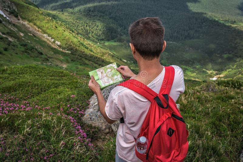 O homem com a trouxa vermelha perdida nas montanhas, guardando o mapa da viagem, pavimenta a rota do turista fotografia de stock royalty free