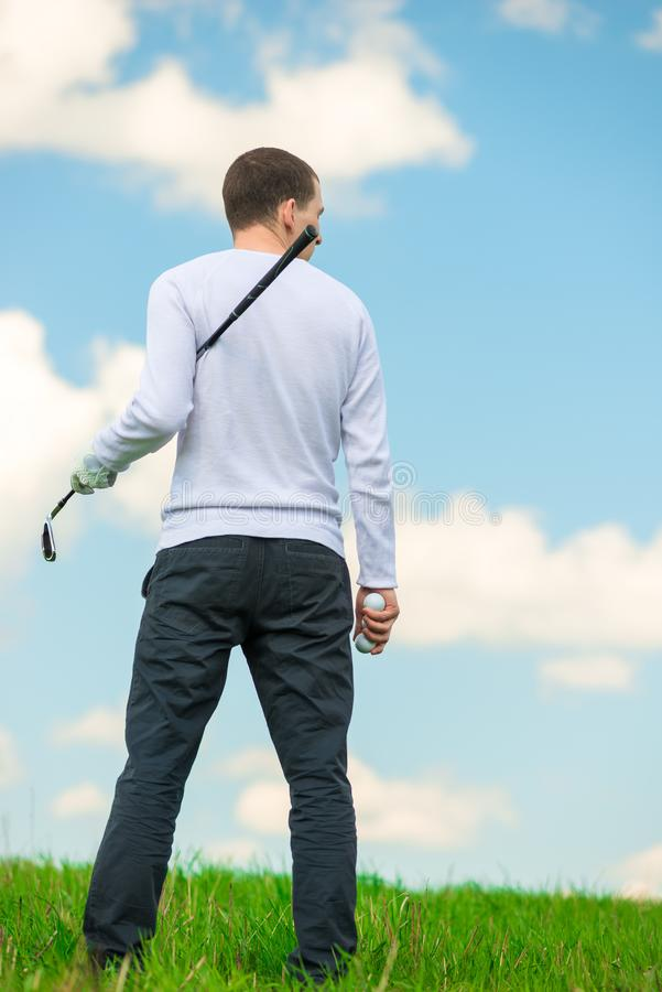 O homem com um clube e as bolas de golfe examina o campo para o jogo, imagem de stock