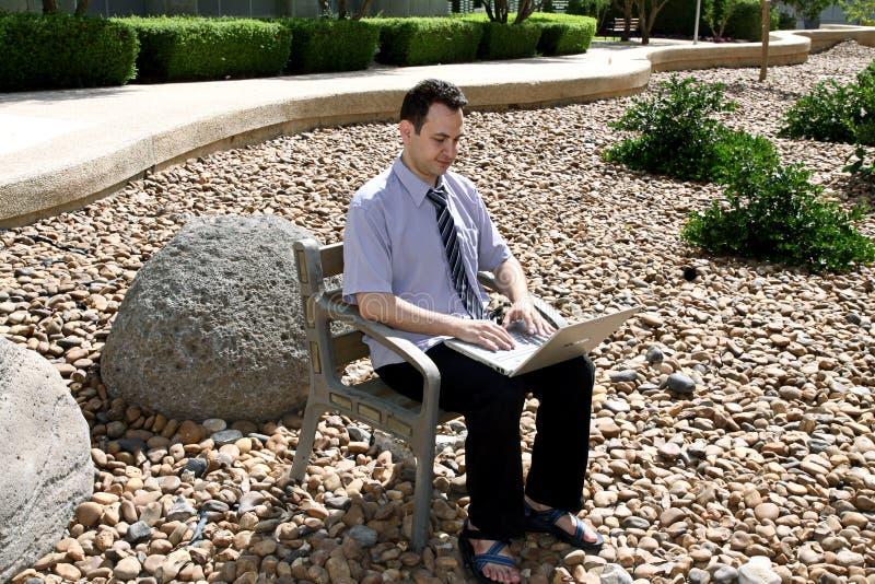 O homem com um portátil senta-se em um jardim de rocha em Ben Gurion University imagens de stock