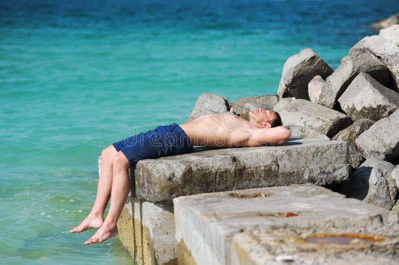 O homem com um torso despido que encontra-se em uma pedra na perspectiva do mar fotos de stock
