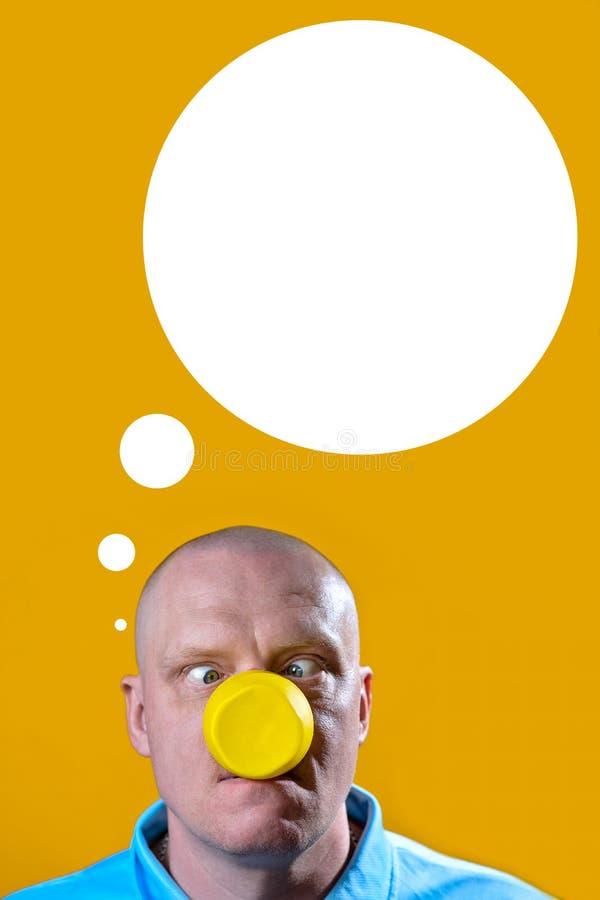 O homem com um vidro amarelo em vez de um nariz deslocou seus olhos em um grupo da surpresa em um fundo amarelo fotos de stock royalty free