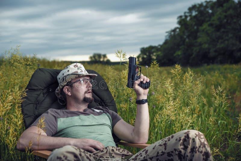 O homem com vidros e uma arma em sua mão está sentando-se em uma cadeira confortável na natureza com um olhar pensativo imagem de stock royalty free