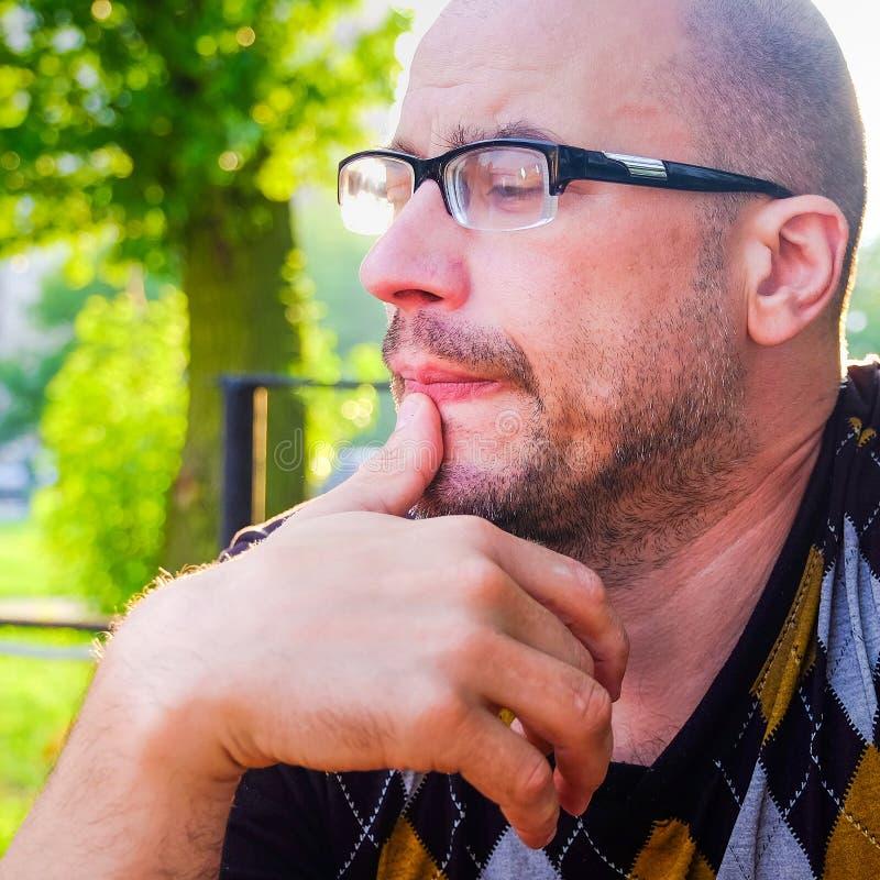 O homem com vidros sofre da depressão Problemas na vida pessoal e no trabalho Esforço e depressão A enxaqueca é fotografia de stock royalty free