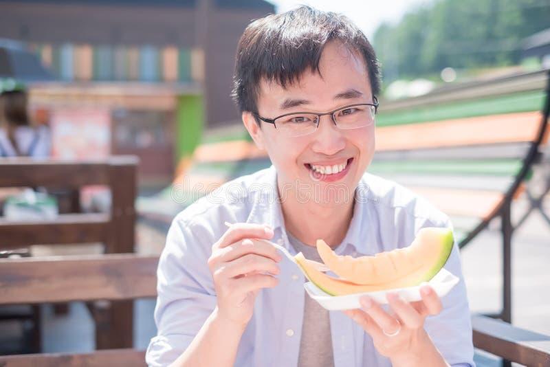O homem come o cantalupo imagens de stock