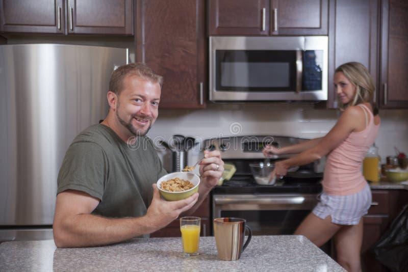 O homem come o cereal quando a senhora fizer o café da manhã fotos de stock