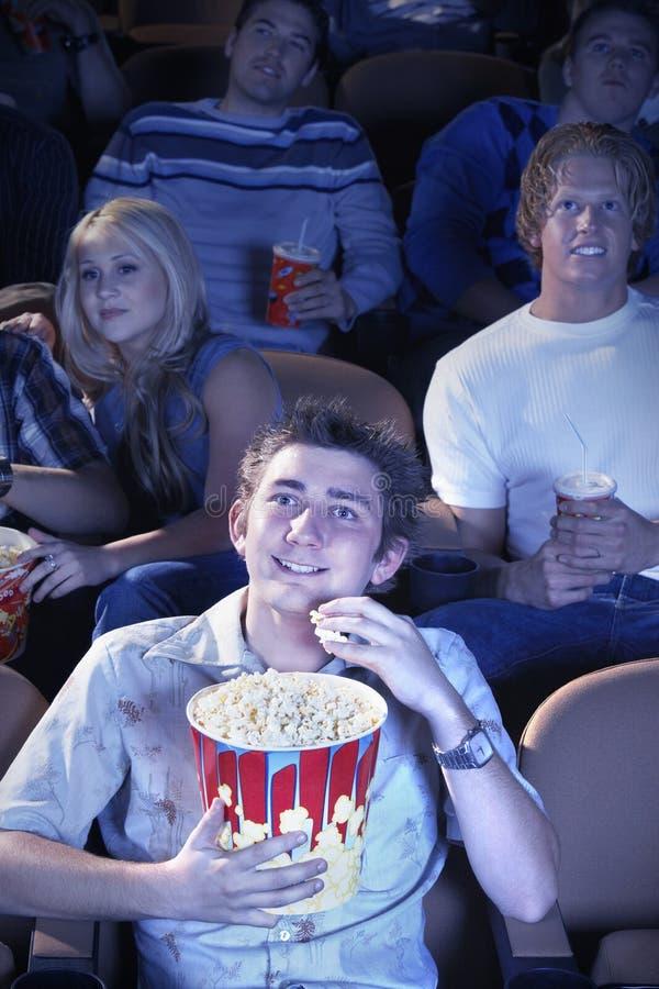O homem come a pipoca ao olhar o filme no teatro fotos de stock