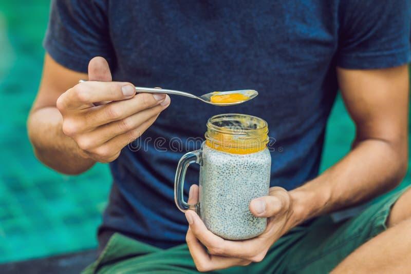 O homem come a sobremesa com sementes e manga do chia pela associação na manhã comer saudável, alimento do vegetariano, dieta e c imagem de stock royalty free