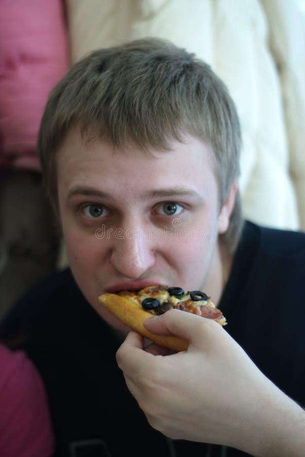 O homem come uma pizza imagens de stock royalty free