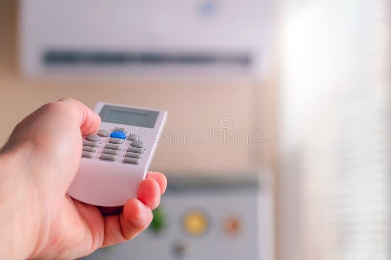O homem comuta os modos do condicionamento de ar Telecontrole à disposição Ajusta a temperatura refrigerando da sala foto de stock