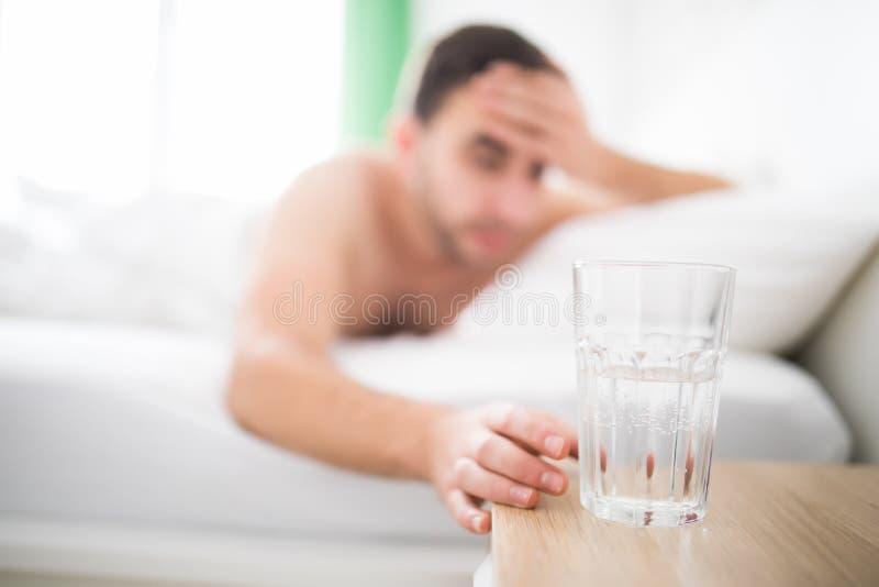 O homem considerável acorda com dor principal sofre da dor de cabeça e estende para obter um vidro da água em sua cama imagens de stock royalty free