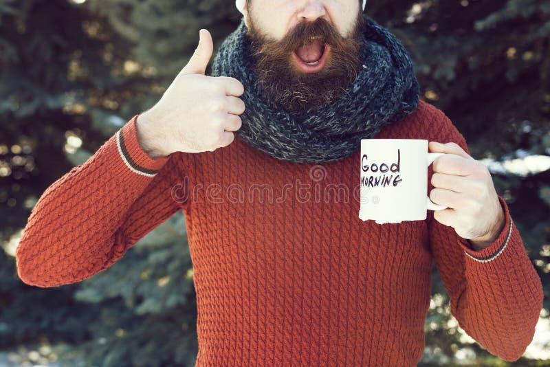 O homem considerável alegre, o moderno farpado com barba e o bigode dão os polegares acima do gesto de mão com texto do bom dia s fotografia de stock royalty free