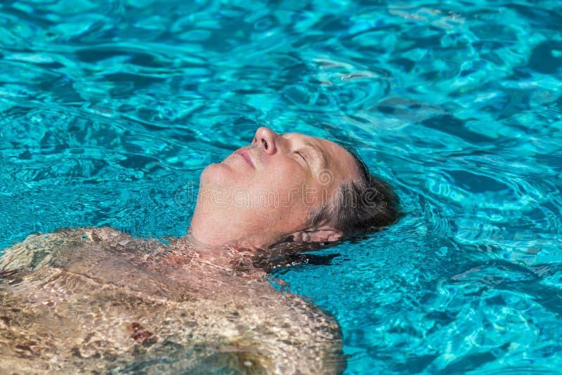 O homem considerável aprecia nadar na associação fotografia de stock
