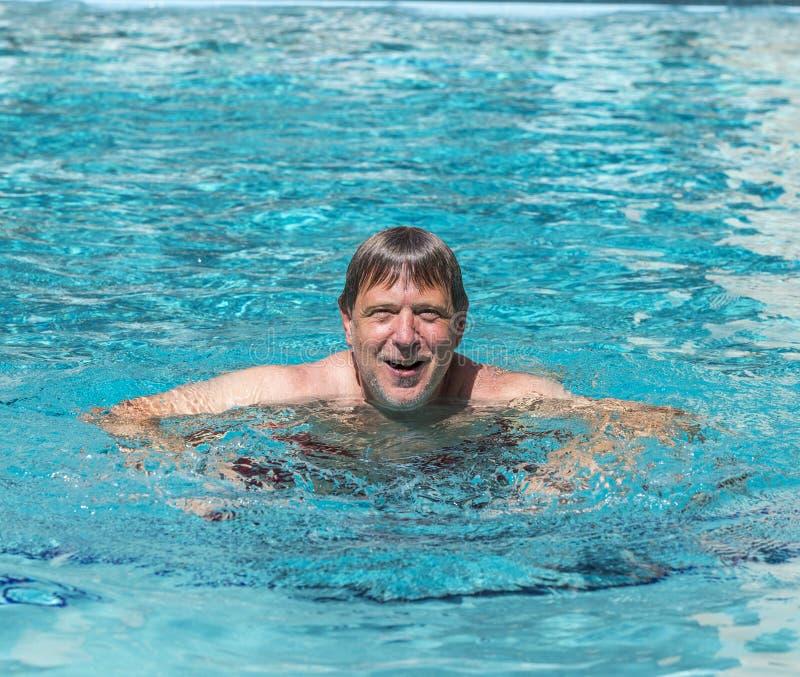 O homem considerável aprecia nadar na associação fotos de stock