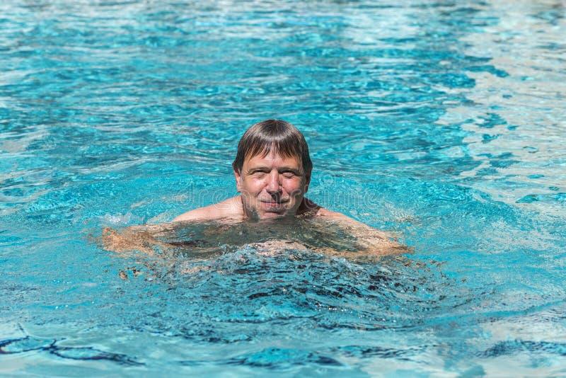 O homem considerável aprecia nadar na associação foto de stock