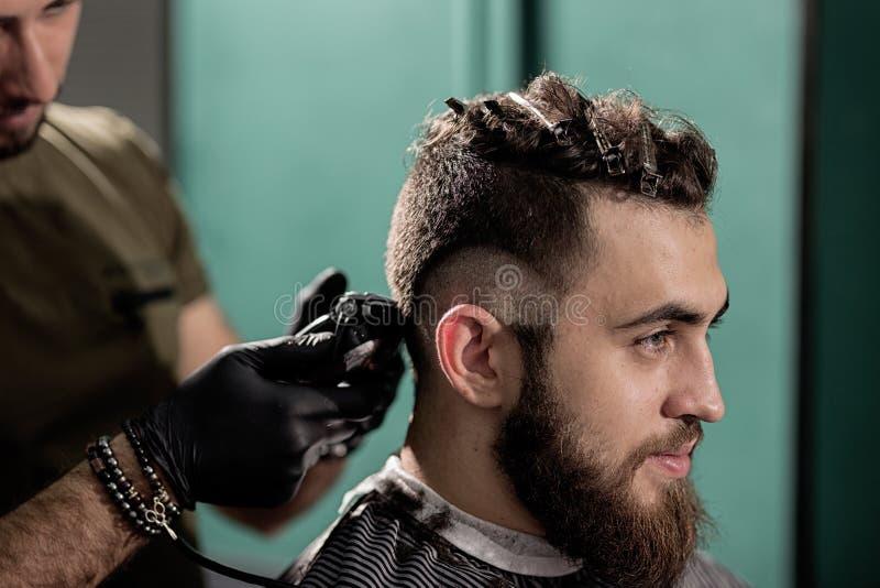O homem considerável brutal com barba senta-se em uma barbearia O barbeiro barbeia os cabelos no lado imagens de stock