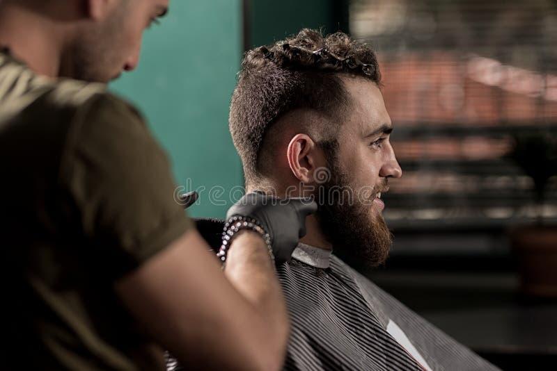 O homem considerável brutal com barba senta-se em uma barbearia O barbeiro barbeia os cabelos no pescoço fotos de stock royalty free