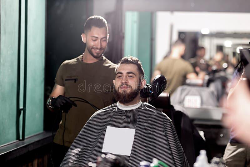 O homem considerável com barba senta em uma barbearia na parte dianteira o espelho O barbeiro faz uma guarnição do cabelo fotos de stock