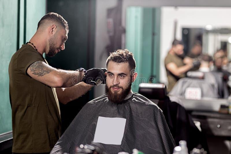 O homem considerável com barba senta em uma barbearia na parte dianteira o espelho O barbeiro faz uma guarnição do cabelo imagem de stock royalty free
