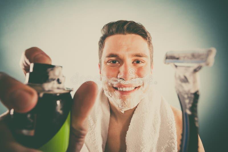 O homem considerável com espuma do creme de rapagem pode e lâmina foto de stock