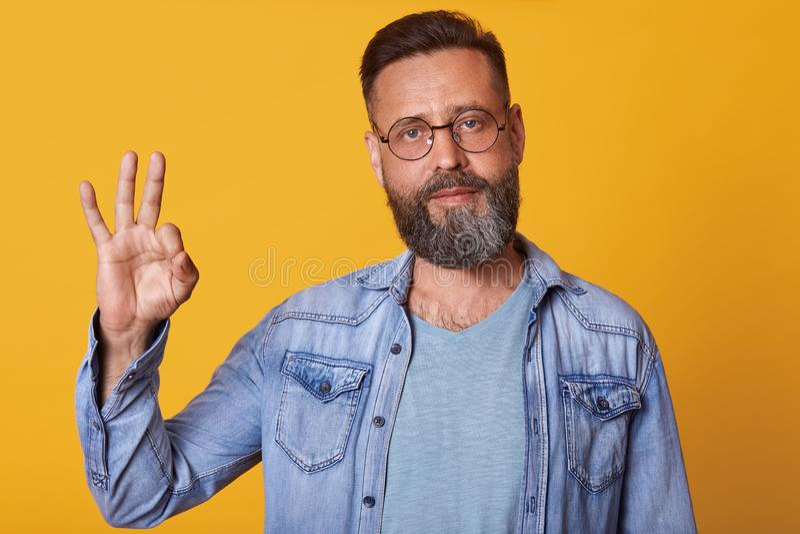 O homem considerável com o revestimento vestindo da sarja de Nimes da barba e a camisa cinzenta de t está contra a parede amarela imagens de stock