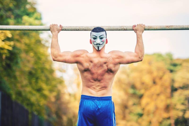 O homem considerável descamisado que faz o queixo levanta no parque, vestindo uma máscara do anonymus Jogador da aptidão, instrut imagens de stock royalty free