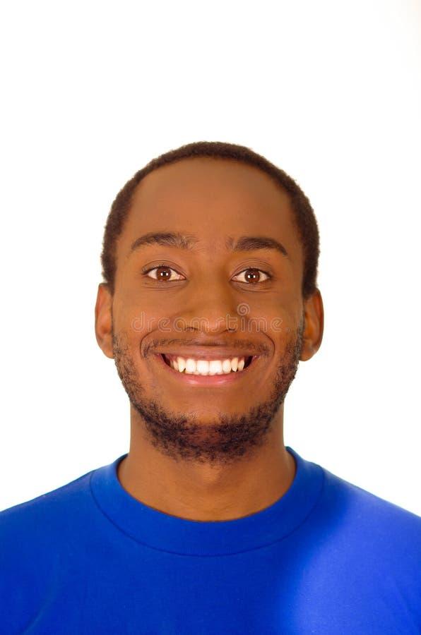 O homem considerável do Headshot que veste o azul forte coloriu o t-shirt que sorri à câmera, fundo branco do estúdio imagens de stock