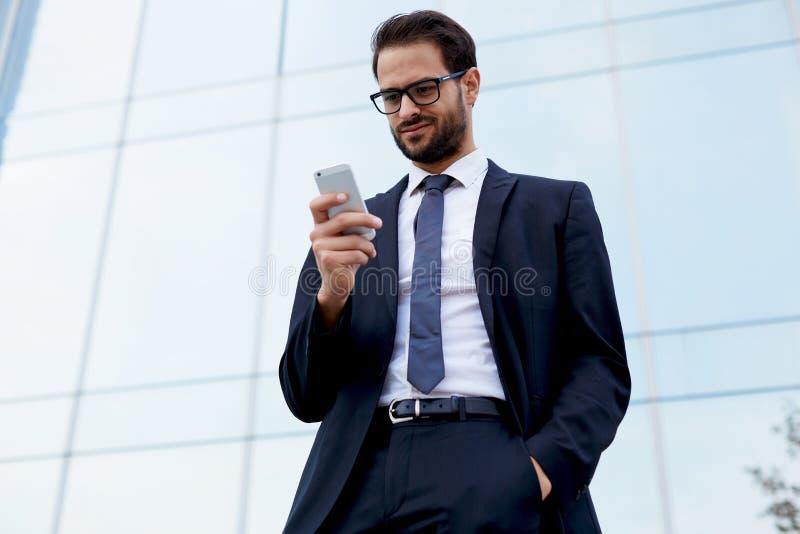 O homem considerável em um terno à moda lê uma mensagem de um suporte favorito ao lado do prédio de escritórios imagens de stock royalty free
