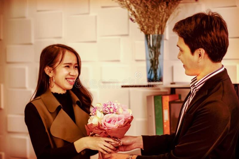O homem considerável envia um sorriso ao ramalhete congratulatório das rosas, dá a uma menina um amante feliz, estilo do vintage  foto de stock royalty free