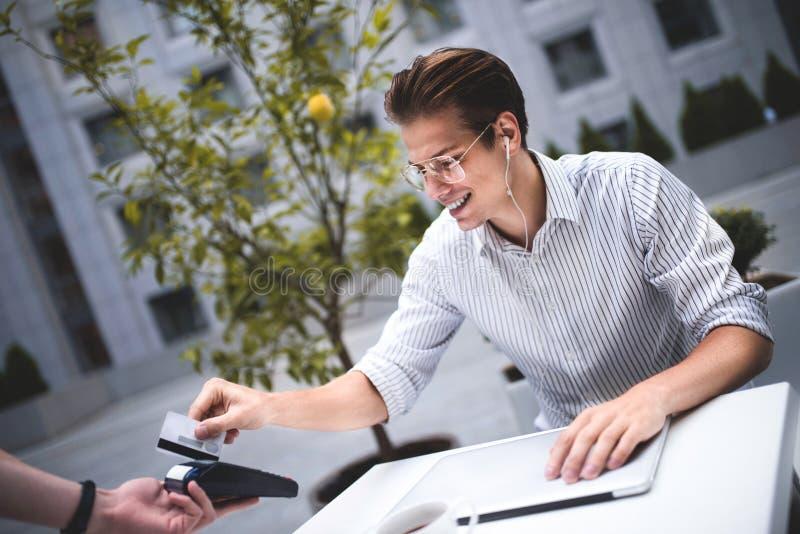 O homem considerável está dando um cartão de crédito no café da cidade fotos de stock