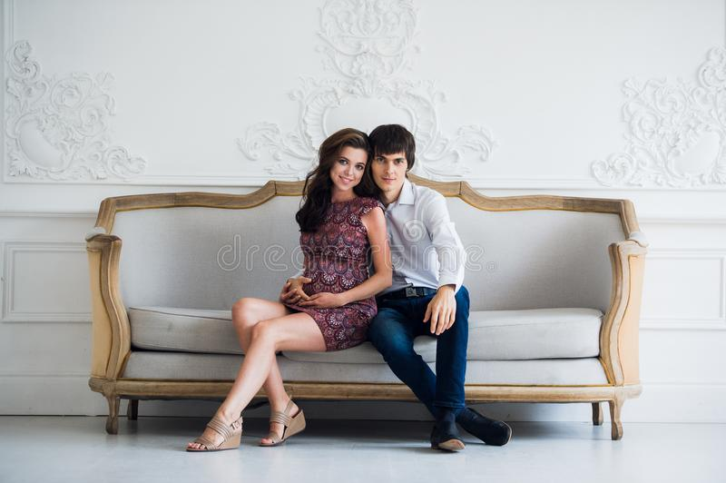 O homem considerável está escutando seus barriga e sorriso grávidos bonitos do ` s da esposa fotografia de stock