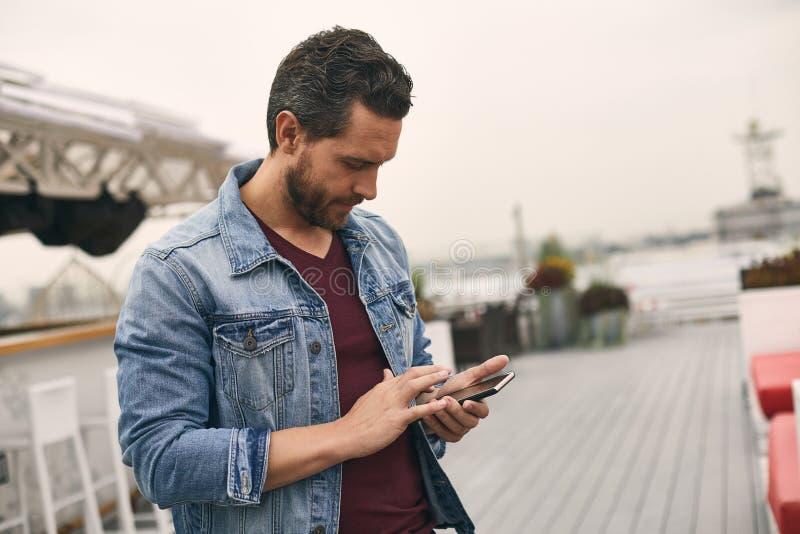 O homem considerável está estando exterior e está guardando o telefone imagem de stock royalty free