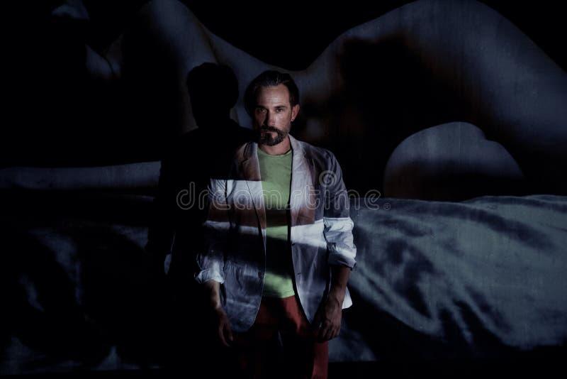 O homem considerável está nas sombras na frente da parede foto de stock
