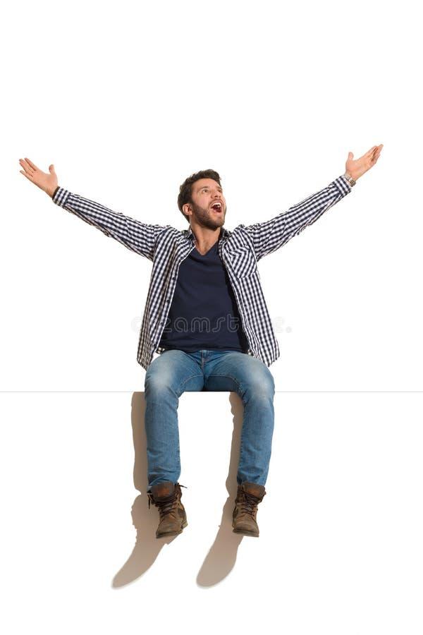 O homem considerável feliz está sentando-se em uma parte superior com os braços estendidos, olhando acima e a gritaria imagens de stock royalty free