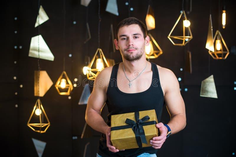 O homem considerável na camiseta de alças preta guarda um presente em suas mãos, abre um presente, presente fotografia de stock royalty free