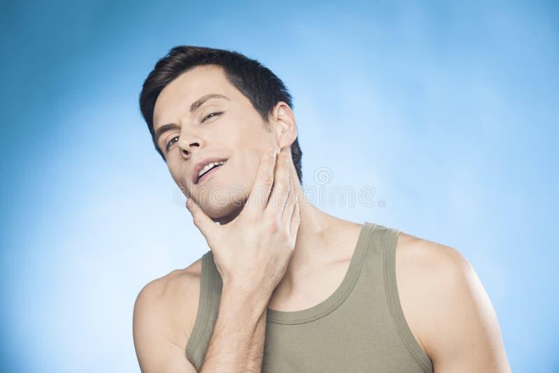 O homem considerável na camiseta de alças verde na frente do espelho que olha sua verificação do queixo é ele bem-barbeou imagens de stock royalty free
