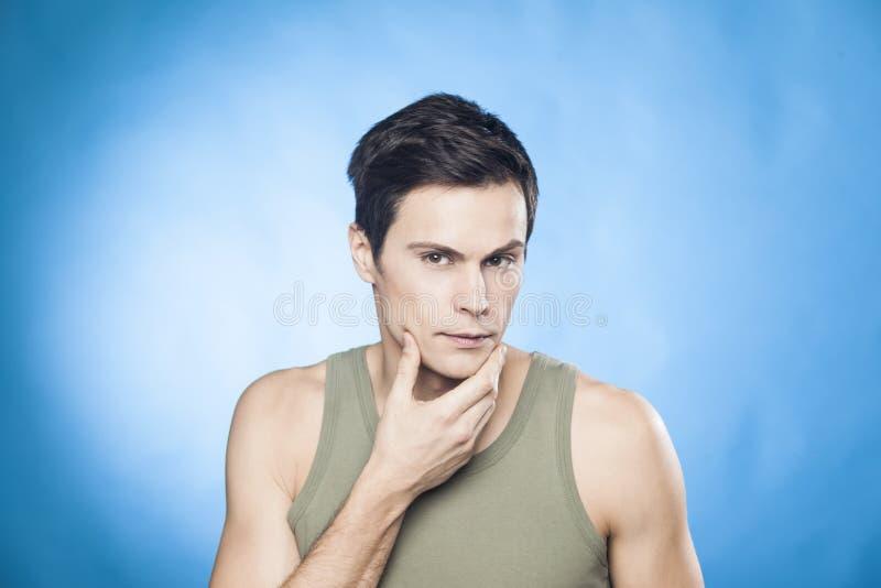 O homem considerável na camiseta de alças verde na frente do espelho que olha sua verificação do queixo é ele bem-barbeou fotos de stock