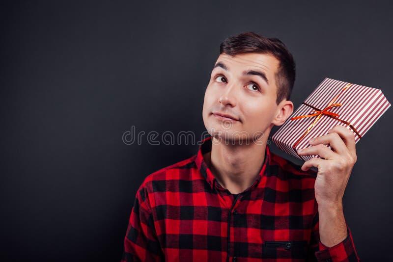 O homem considerável novo agita uma caixa de presente para encontrar que ` s nele foto de stock royalty free