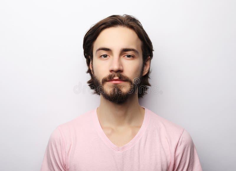 O homem considerável novo com barba, bigode e penteado na moda, veste o t-shirt cor-de-rosa ocasional fotos de stock royalty free