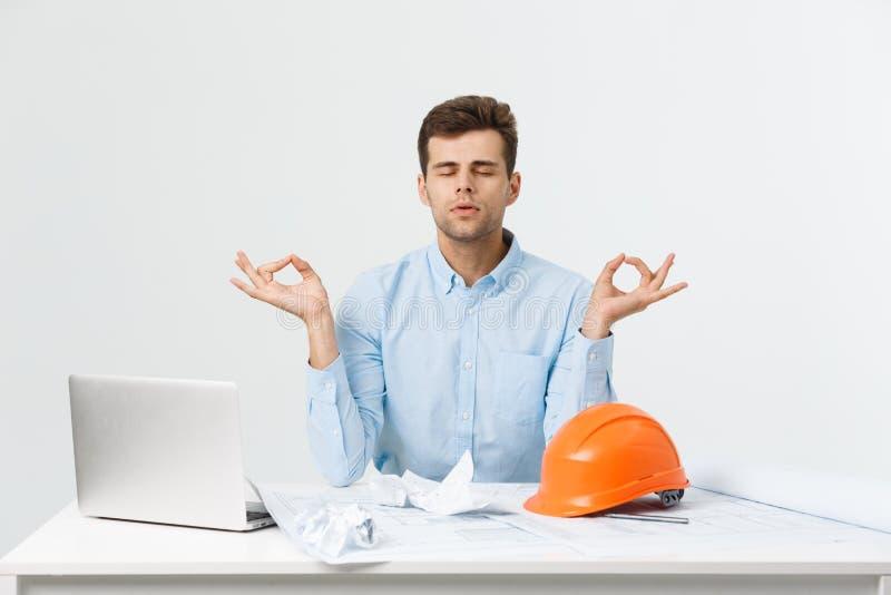 O homem considerável novo do coordenador ou do construtor na ioga azul da prática do terno e relaxa na sala do escritório fotos de stock