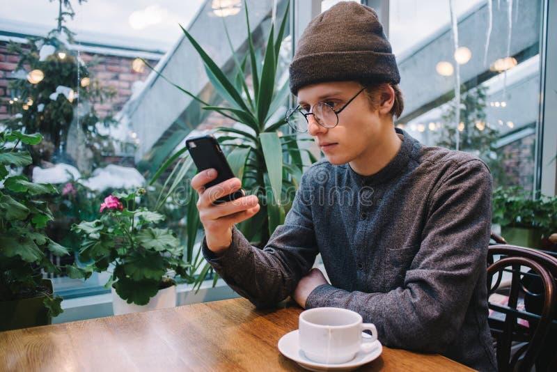O homem considerável novo do moderno usa um telefone celular em um café perto da janela o chá está na tabela, e na estufa da part fotos de stock
