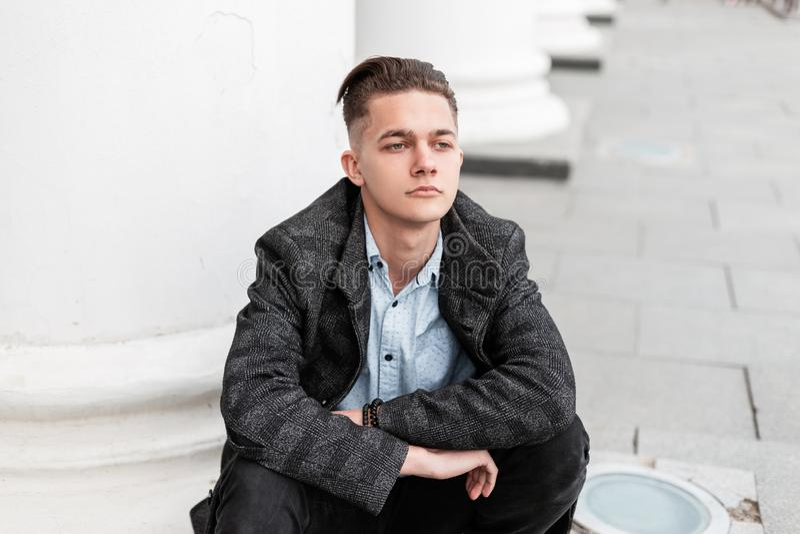 O homem considerável novo em um revestimento na moda da manta em uma camisa à moda nas calças de brim com um penteado elegante se imagens de stock