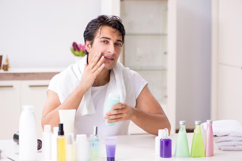 O homem considerável novo no banheiro no conceito da higiene fotografia de stock royalty free