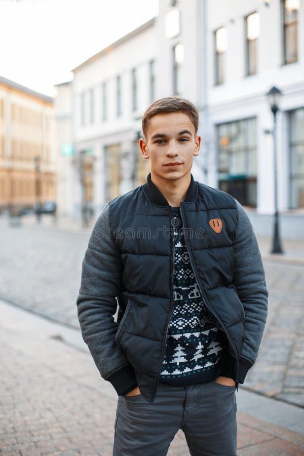 O homem considerável novo no inverno veste a posição perto da construção, imagens de stock royalty free