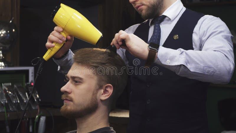 O homem considerável novo que obtém seu cabelo secou por um barbeiro foto de stock