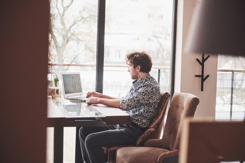 O homem considerável novo que senta-se no escritório com xícara de café e que trabalha no projeto conectou com as tecnologias mod foto de stock royalty free