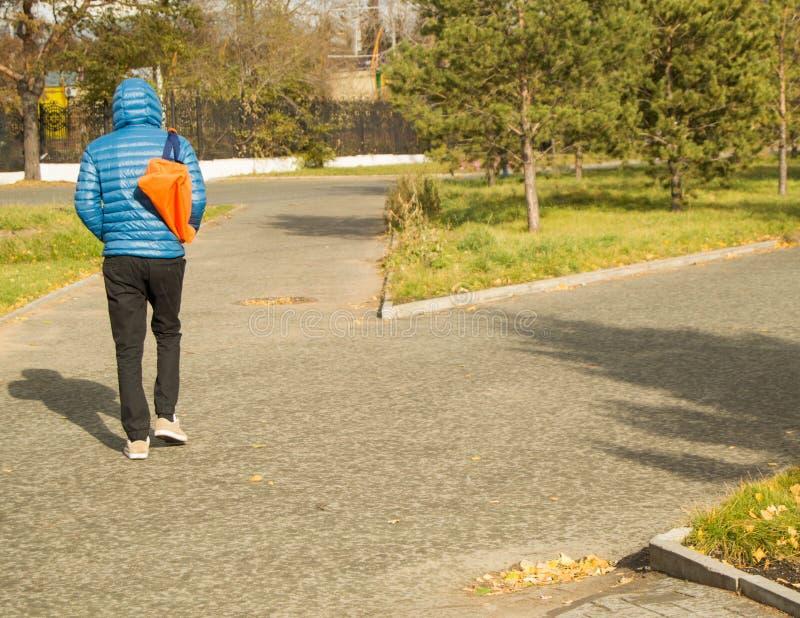 O homem considerável novo que veste um casaco azul com esportes ensaca, andando no parque, vista traseira fotos de stock royalty free