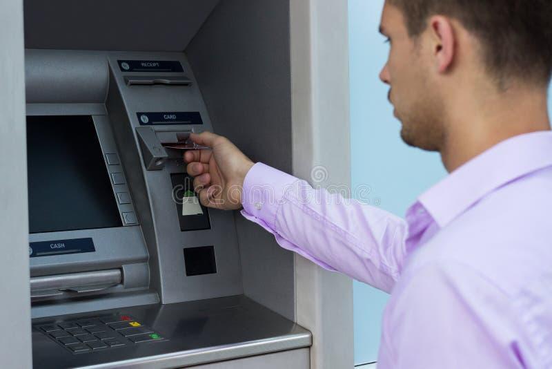 O homem considerável pôs seu cartão de crédito no ATM fotos de stock royalty free
