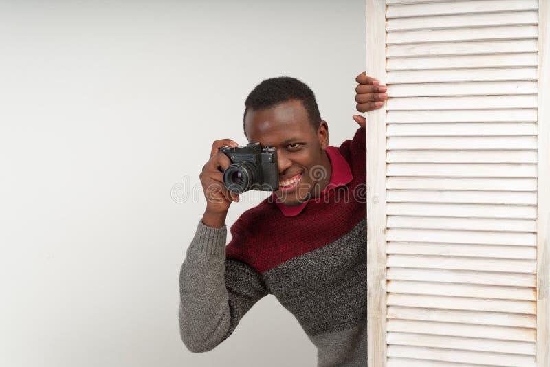 O homem considerável preto correspondente que toma imagens de uma cena picante, faz a notícia intrigante, que não é sabida ainda  imagem de stock royalty free